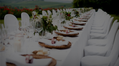 event planning photo of long white table with white chairs and place settings