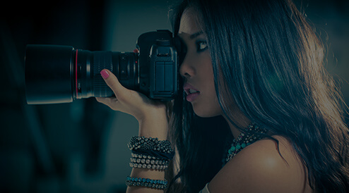 tan girl with dark hair holding a large camera and taking a picture